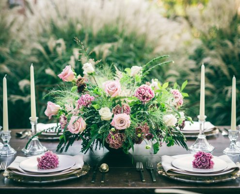 Dusty rose and blush centerpiece on a farm table