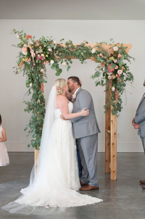 bride-groom-kiss-ceremony-arbor