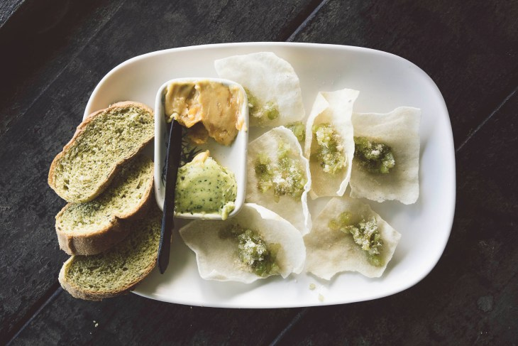 zestaw darmowych przystawek - od lewej: na miejscu pieczony chleb, zielone masełko z pesto, żółte masełko z mango oraz chipsy z manioku z pomidorową salsą z dodatkiem pesto