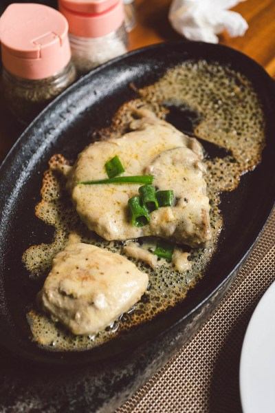 Kotlety wieprzowe podane na skwierczącym talerzu (sizzling)