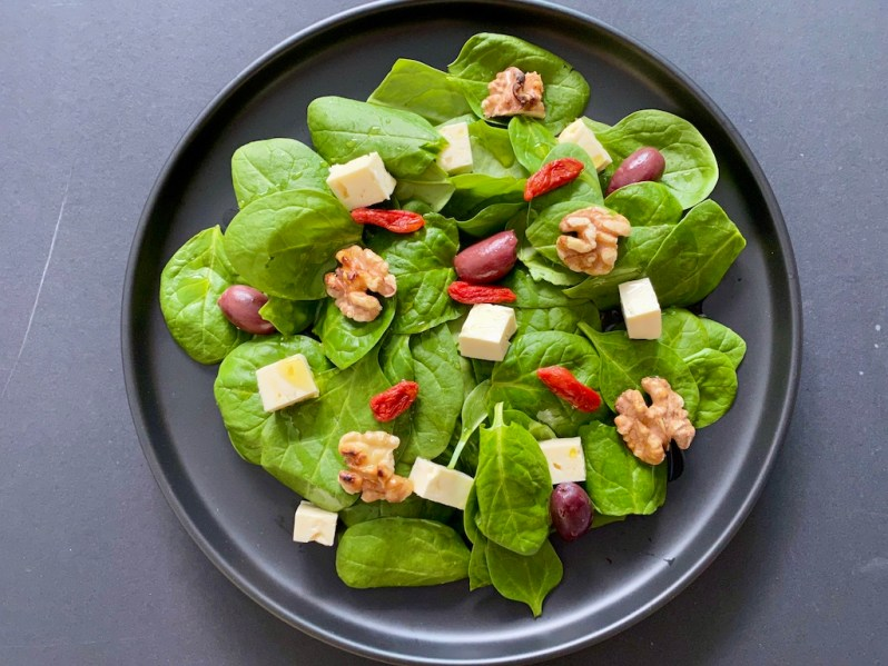 Healthy baby spinach leaves salad with feta cheese and goji berries