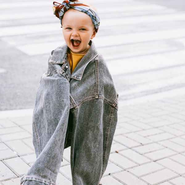 smilling baby in an oversize denim jacket