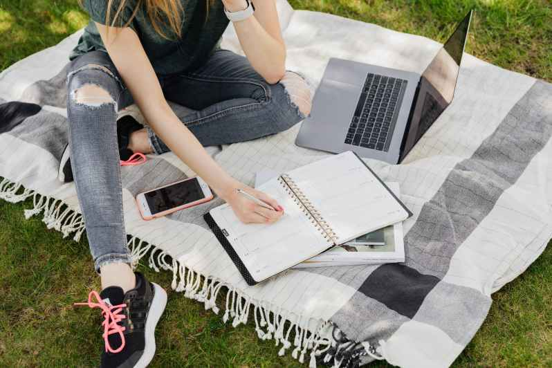 woman with planner and laptop sitting on blanket in park