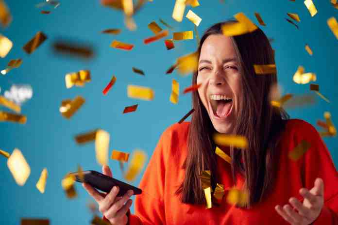 Celebrating Young Woman With Mobile Phone Winning Prizes And Showered With Gold Confetti In Studio