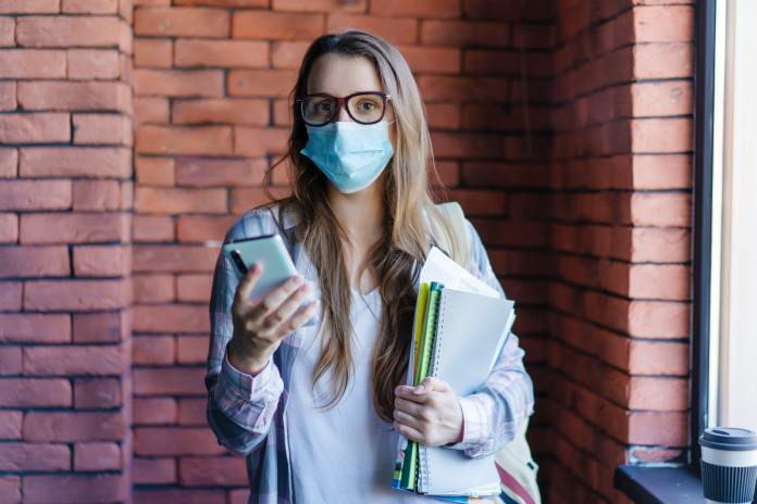 female student in protective medical mask with phone and textbooks in college.