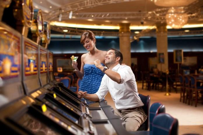 man and woman playing he slot machine