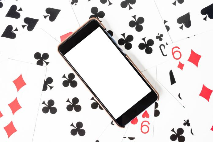 Smart phone with white screen on playing cards background.