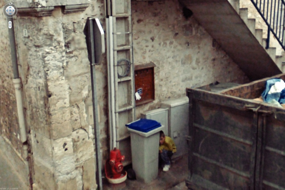 15 Crazy Moments Captured on Google Street View - Boy Hiding Behind Trash Can