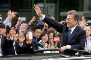 South Korean President Moon Jae-in waves from a car after inauguration. Reuters.