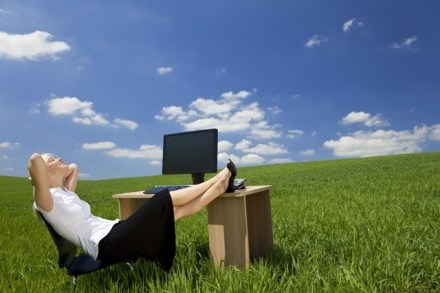Business concept shot of a beautiful young woman relaxing at a desk in a green field with a bright blue sky. Shot on location.