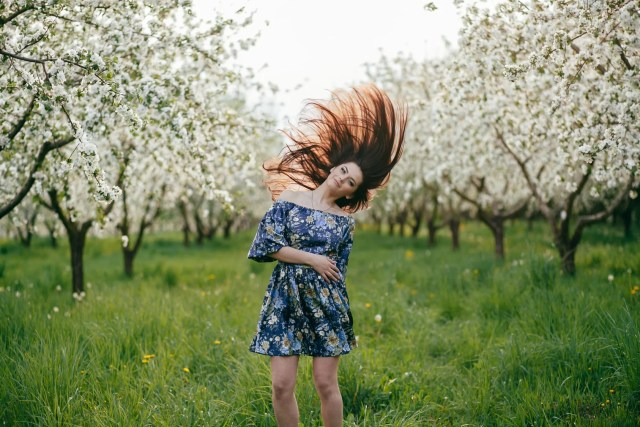 Spring walk girl in a beautiful cherry orchard