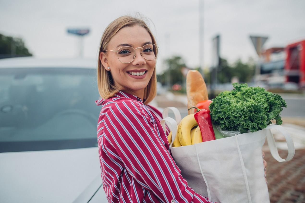 Dziewczyna trzyma papierowa torbę z produktami wegańskimi
