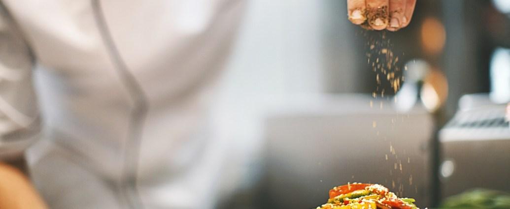 Kucharz doprawia danie pikantnymi przyprawami
