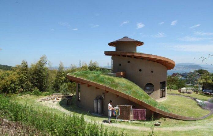 Casa ecológica en espiral construida con madera, tierra y techo verde.