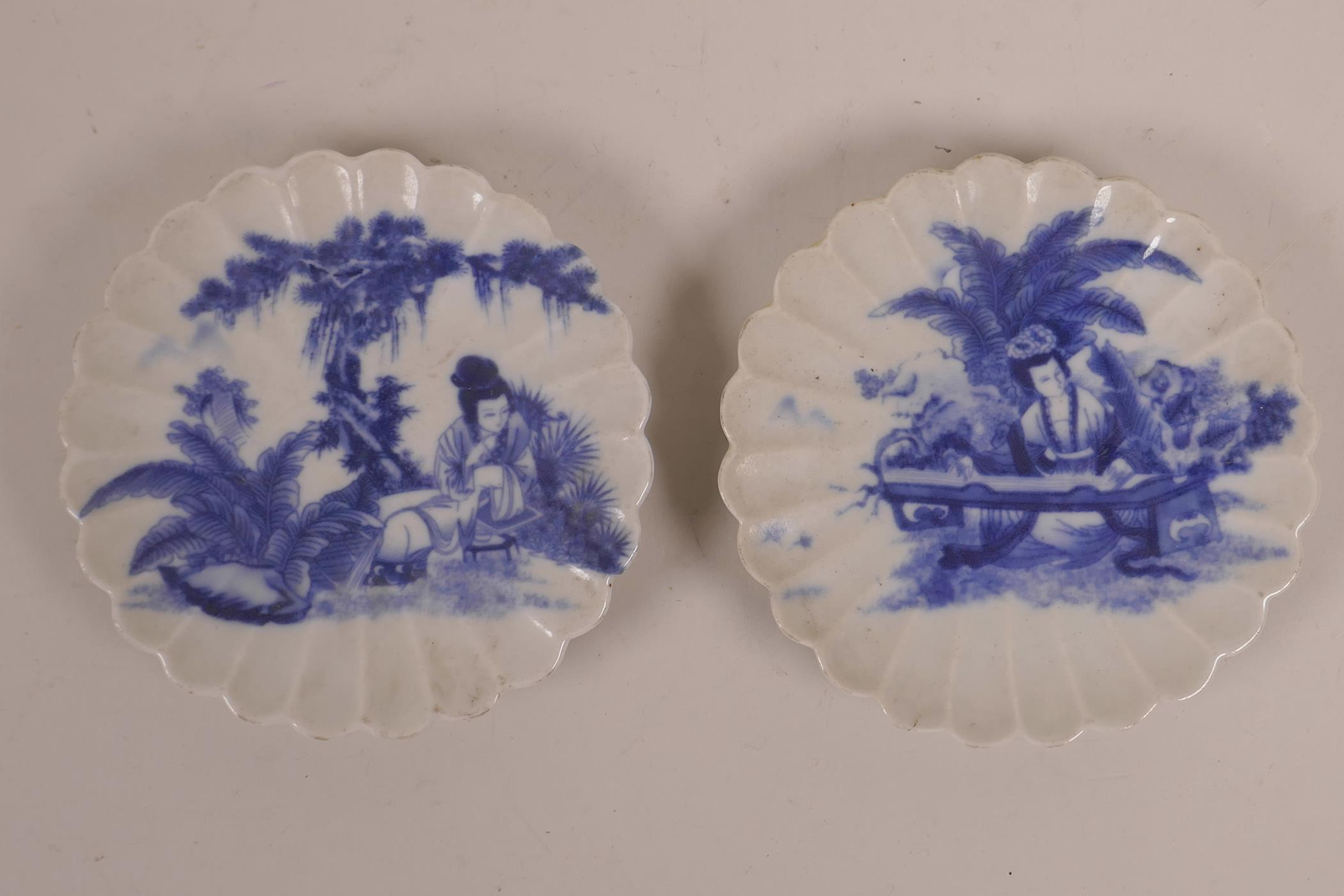 Lot 103 - A pair of Chinese blue and white porcelain petal shaped saucers decorated with women of leisure in a