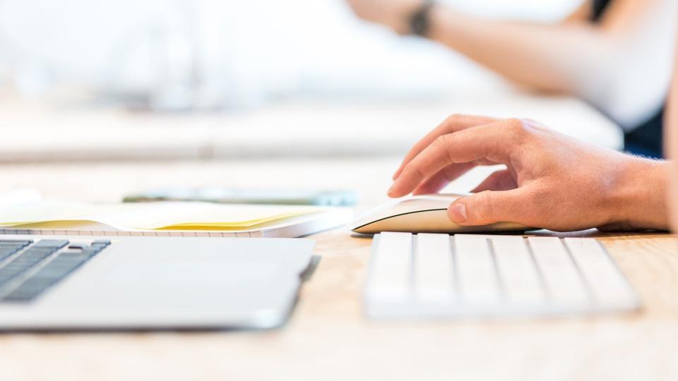 Estágio: mão segurando o mouse em frente teclado de computador
