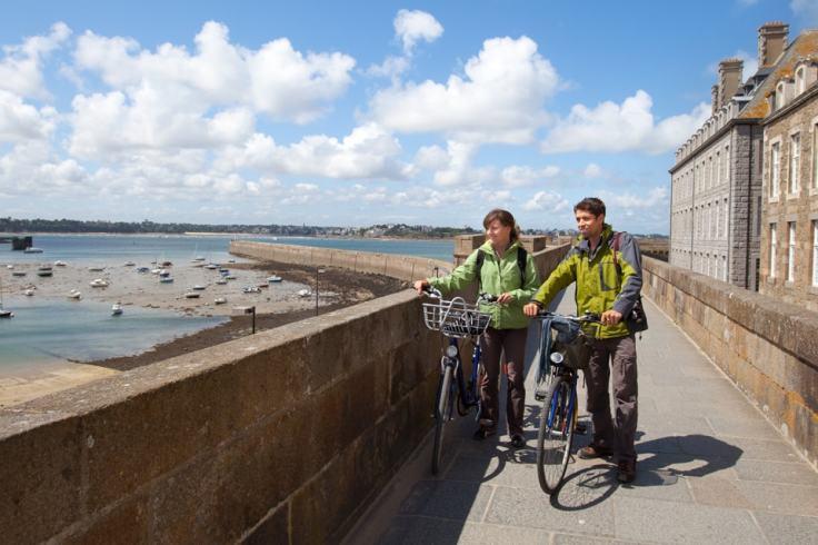 Deux jeunes adultes en vélo sur les remparts de la ville de Saint-Malo
