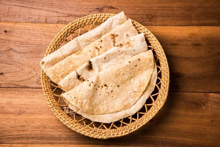 Des chapatis sont disposés dans un plat tressé.