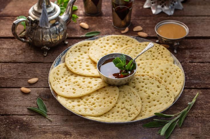 Assiette de baghrirs, avec du miel et du thé à la menthe.