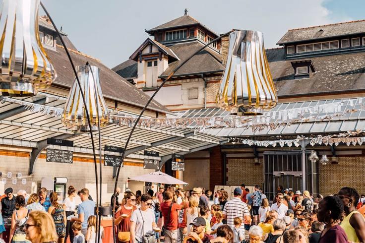 De nombreuses personnes présentent au Marché à Manger de Rennes. Elles font la queue aux stand et mangent sur de grandes tables.