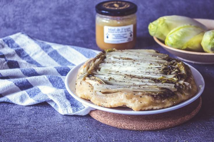 Tarte tatin d'endives prête à être dégustée, avec pot de miel et endives crues.