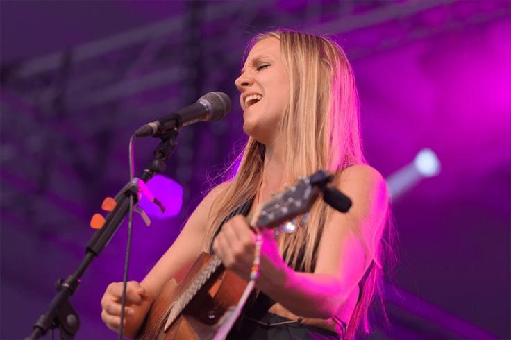 Aziliz Manrow chantant avec une guitare au festival de Cournouaille