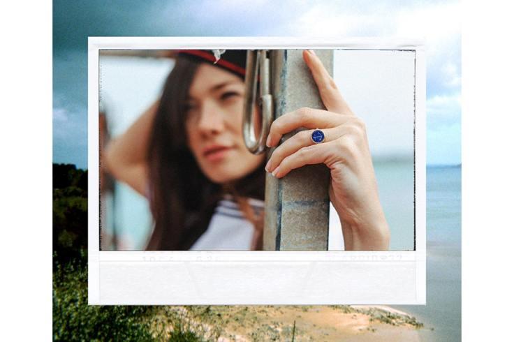 Une fille au bord de la mer avec une bague bleu