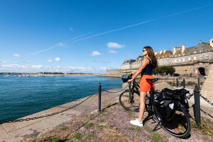 Une femme est sur son vélo et regard l'horizon. Elle est sur les quais de Saint-Malo tout près du château hôtel du Colombier.