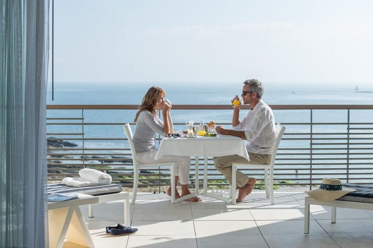 Un couple prend son petit déjeuner face à la mer