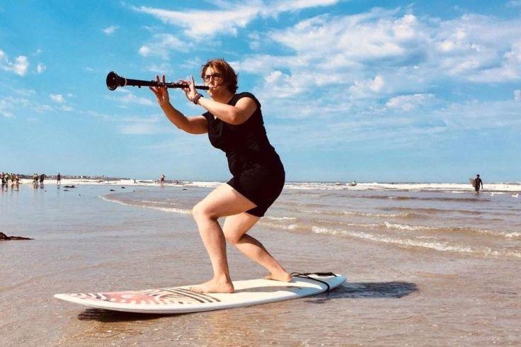Une musicienne sur une planche de surf