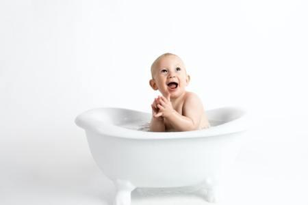 Un enfant chante des comptines dans son bain et fait des jeux de doigts.