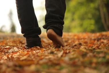 marcher pieds nus sur un tapis de feuille en automne.