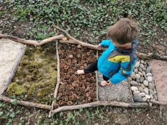Samuel dépose son pied sur les pommes de pin.