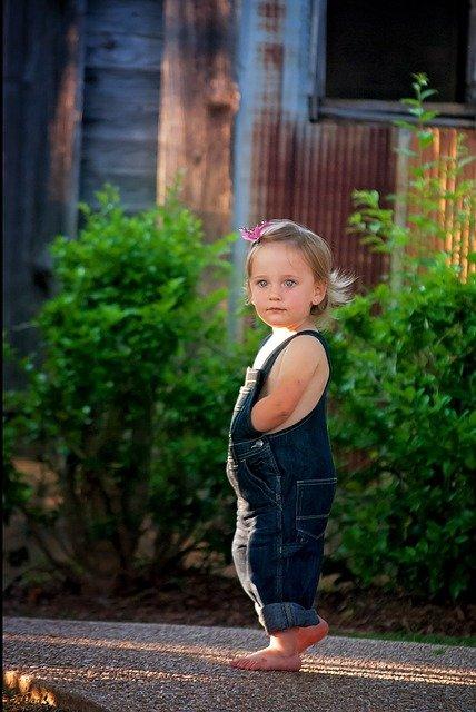 une petite fille marche sur un chemin goudronné.