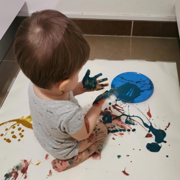Un enfant regarde la peinture bleue sur ses mains.