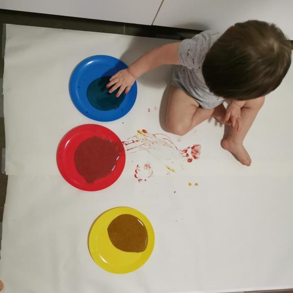 Un enfant met de la peinture sur ses mains avant de commencer l'activité en famille.