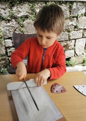 Un enfant fabrique une castagnette avec une latte de lit.