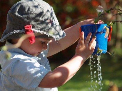 Un enfant fait un jeu d'eau en extérieur.