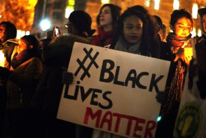 Black woman holding up a sign at a protests that says #BlackLivesMatter