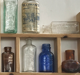 A close-up of the bottle display at Marmalade Antiques, Falmouth. Cornflower-blue bottle.