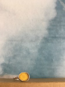 Yellow seaglass ring shown with clouds behind