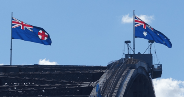 The New South Wales and Australia flags fly on the Sydney Harbor Bridge.