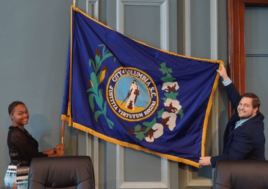 Columbia's media relations staff show the flag in the city council chambers. Adopted in 1912, it features the city seal and stalks of corn and cotton.