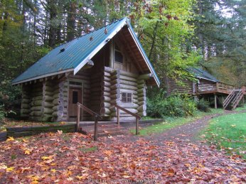 There three log cabins around an open grass area to provide bunk houses for campers.