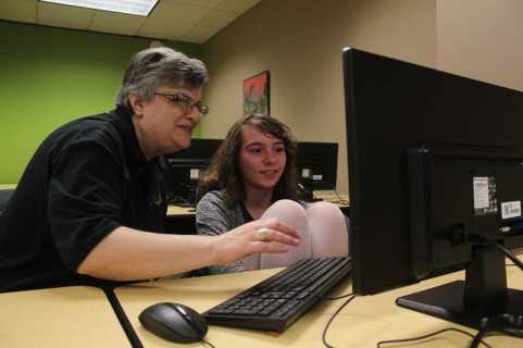 CONNECTION PHOTO: KELSEY O'HALLORAN - Fidgets2Widgets co-founder Pam Sullivan, left, helps Deer Creek Elementary fifth-grader Gianna Bennett in the program's computer lab, where students play games such as Minecraft and work on homework.