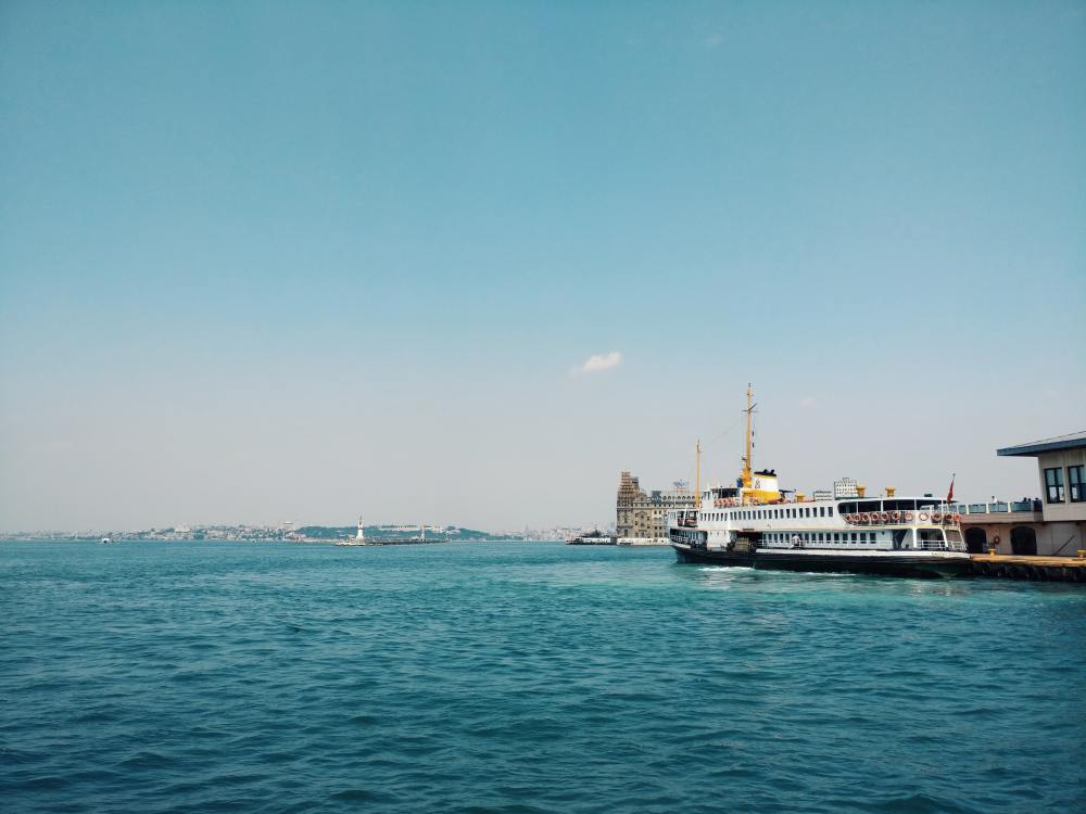 white and black ship on sea under blue sky during daytime