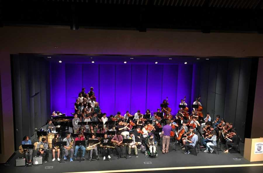 Mr.+Stevens+conducts+his+String+Orchestra+as+they+perform+at+the+Fine+Arts+Assembly.