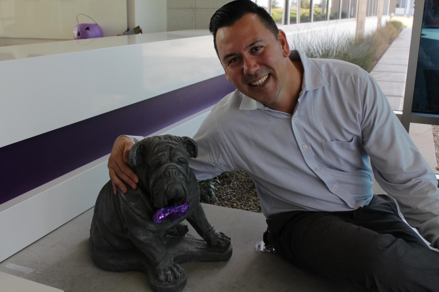 Kris Linville smiles with Buster the Bulldog in the front office.