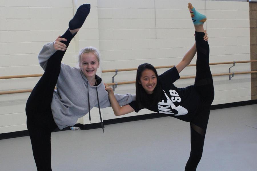 Freshmen Alina Medvedeva (left) and Nena Oshita (right) complete twin leg holds in the dance practice room.
