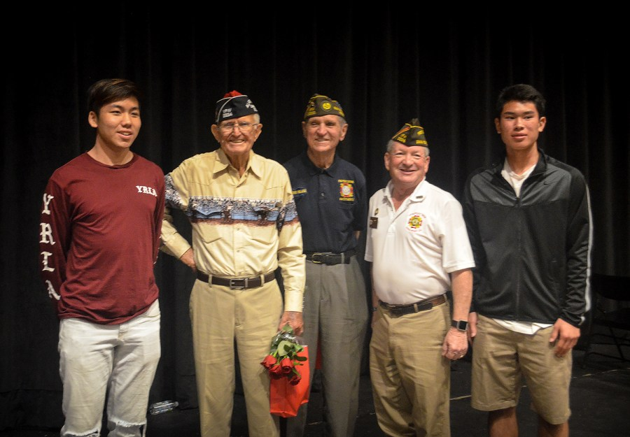 Sophomores Garrett Lim and Patrick Cui take a photo with World War II veterans Bill Hamilton, Loren Major and post commander of The Veterans of Foreign Wars Wayne Yost after the veterans reflected on their experiences in a presentation to the community.